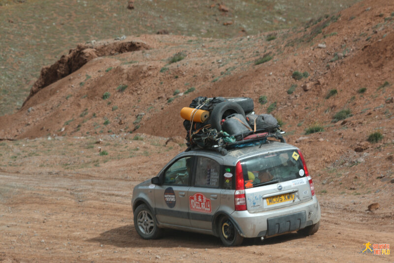Mongol rallye car with four Australians inside, driving on a spare tire with a broken suspension.